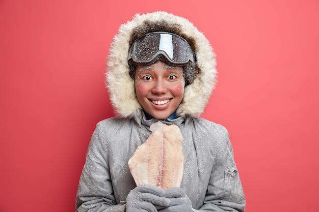 Schneebedeckte glückliche arktische frau lächelt breit trägt mantel mit kapuze und warme handschuhe hält gefrorenen fisch froh, nachdem skifahren angeln oder snowboarden während der winterzeit. aktives ruhe-hobby-konzept