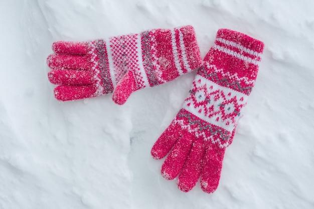 Schneebedeckte handschuhe auf schnee, winterhintergrund.