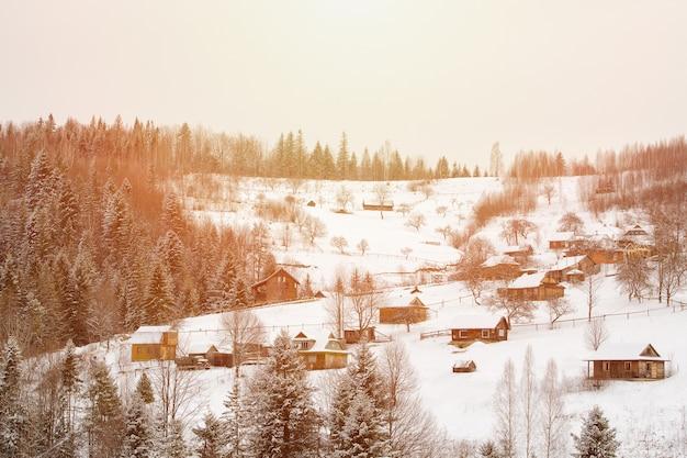 Schneebedeckte hügel, wald und häuser in der ferne. winterlandschaft