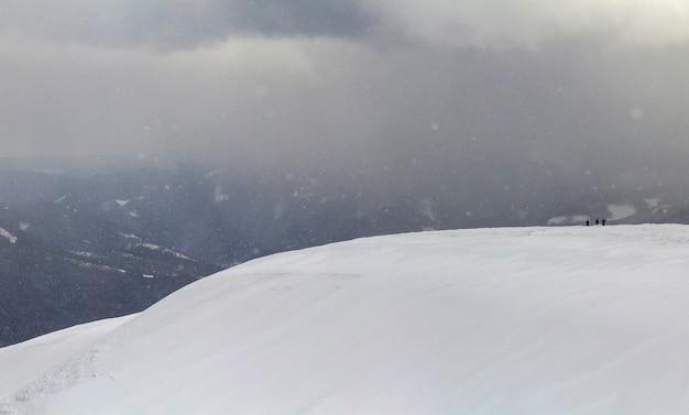 Schneebedeckte karpatengebirgshügel mit weit entfernten wanderertouristen im winter