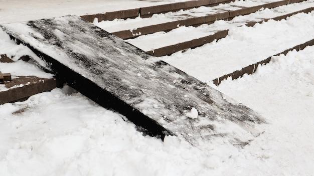Schneebedeckte rutschige betontreppe und holzrampe. erster schnee auf granitsteinstufen.