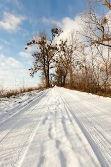 Schneebedeckte straße, auf der spuren des autos zu fahren waren. foto nahaufnahme, tiefe furchen auf einem hintergrund des blauen himmels an einem sonnigen tag