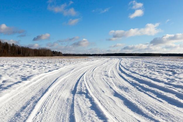 Schneebedeckte straße, auf der spuren des autos zu fahren waren