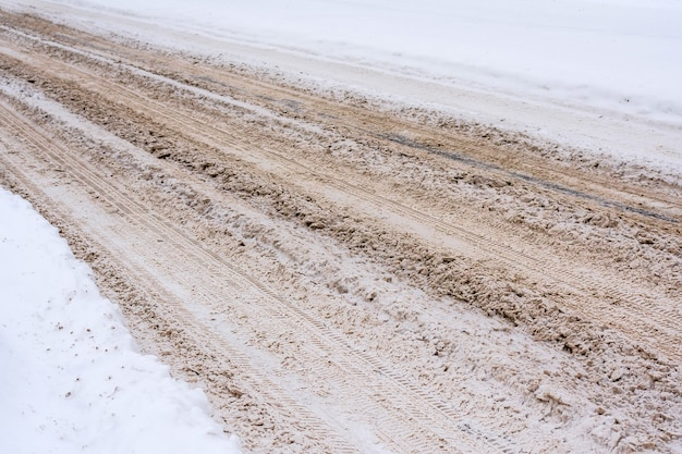 Schneebedeckte straße gemischt mit schlamm, salz, chemischen reagenzien und spuren von autos.