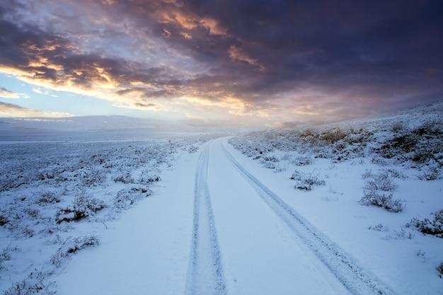 Schneebedeckte straße im winter bei sonnenuntergang