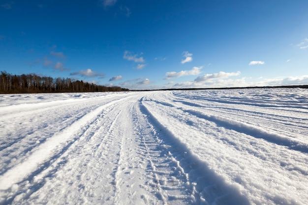 Schneebedeckte straße in der wintersaison. sichtbare spuren des autos. himmel im hintergrund