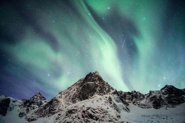 Schneebedeckter berg mit aurora borealis, der mit sternschnuppe in nordland tanzt