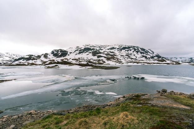 Schneebedeckter berg mit einem kalten fluss in norwegen