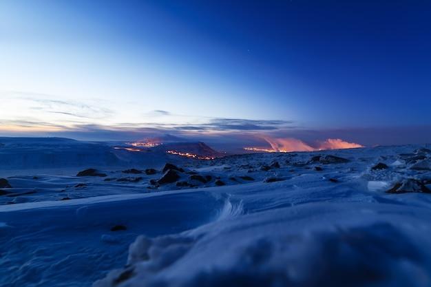 Schneebedeckter berghang, nachtfoto. in der ferne die stahlwerke. russischer hoher norden.