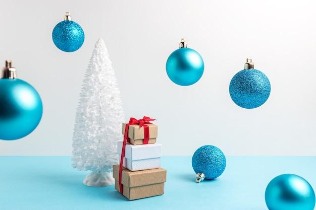 Schneebedeckter weihnachtsbaum mit weihnachtsdekoration und geschenkboxen auf blauem tisch