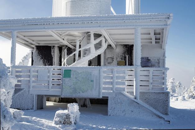 Schneebedecktes haus bei rauen winterbedingungen.