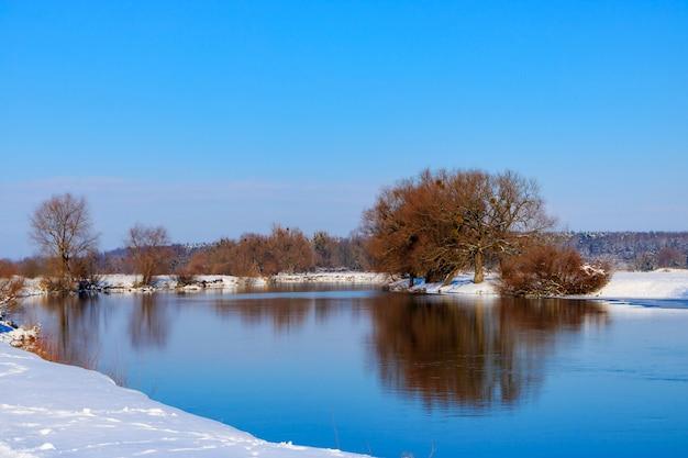 Schneebedecktes ufer des winterflusses bei sonnenuntergang. winterlandschaft