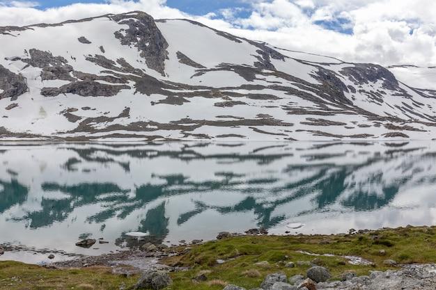 Schneeberge, umgeben von wolken im norwegischen fjordreflex im wasser