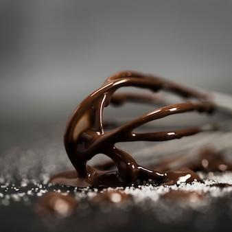 Schneebesen mit geschmolzener schokolade nahaufnahme gefüllt