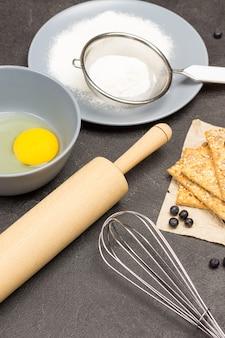 Schneebesen und nudelholz aus metall. eigelb in einer schüssel. mehl und sieb auf grauem teller. kekse auf papier. kochen. schwarzer hintergrund. ansicht von oben