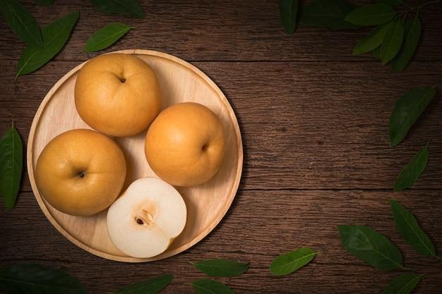 Schneebirne oder fengsui-birne auf einem hölzernen hintergrund, schneebirnenfrüchte köstlich und süß, koreanische schneebirnenfrüchte.