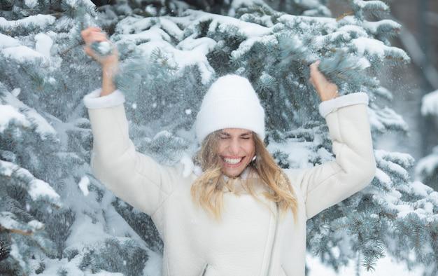 Schneefall. schnee fällt auf den kopf des mädchens. lächelnde frau im winter.