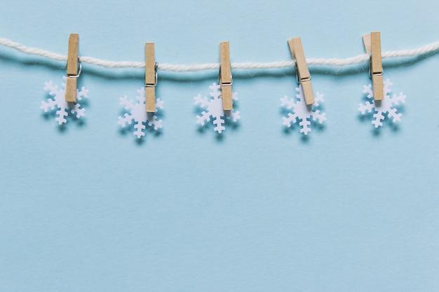 Schneeflocken an einem seil auf blauem hintergrund