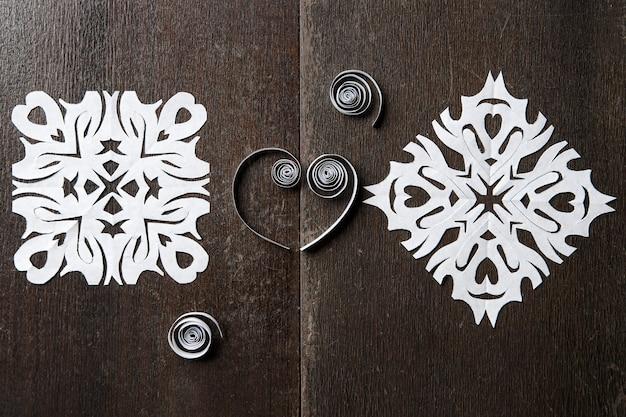 Schneeflocken aus papier auf holz hintergrund weihnachten neujahr