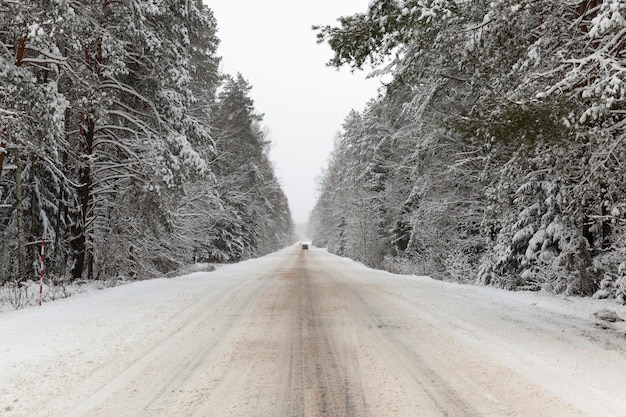 Schneegebundene winterstraße, die durch das gebiet des waldes, winterlandschaft geht