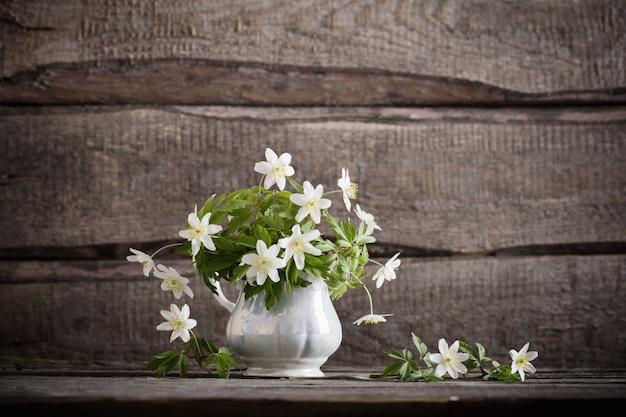 Schneeglöckchen in der vase auf hölzernem hintergrund