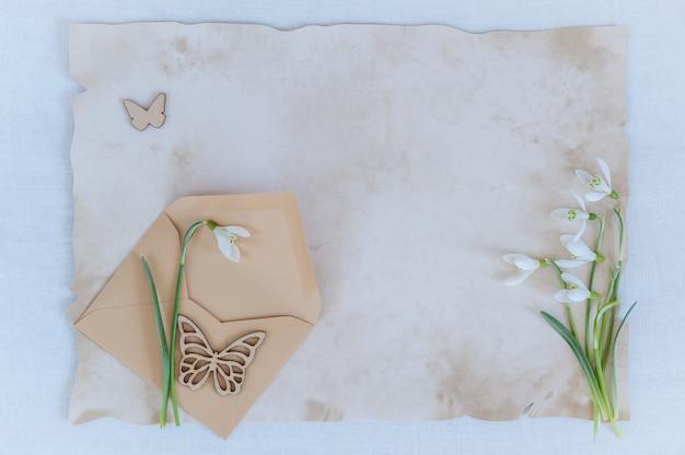 Schneeglöckchen mit umschlag und papier für text auf einem hölzernen hintergrund
