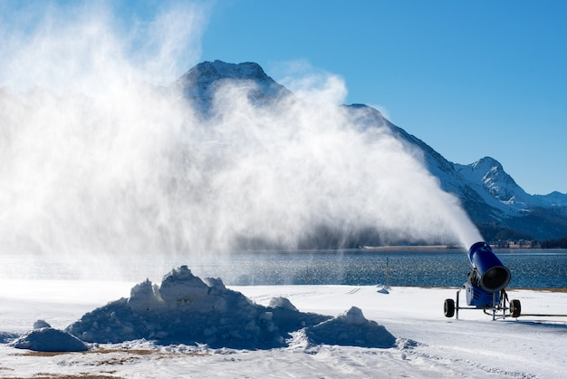 Schneekanone, die nahe bergsee arbeitet
