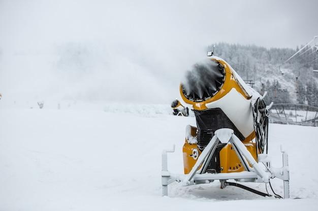 Schneekanone, maschine oder kanone schneit die pisten oder berge für skifahrer und snowboarder, kunstschnee