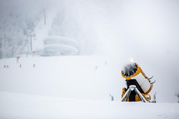 Schneekanone, maschine oder kanone schneit die pisten oder berge für skifahrer und snowboarder, kunstschnee Premium Fotos