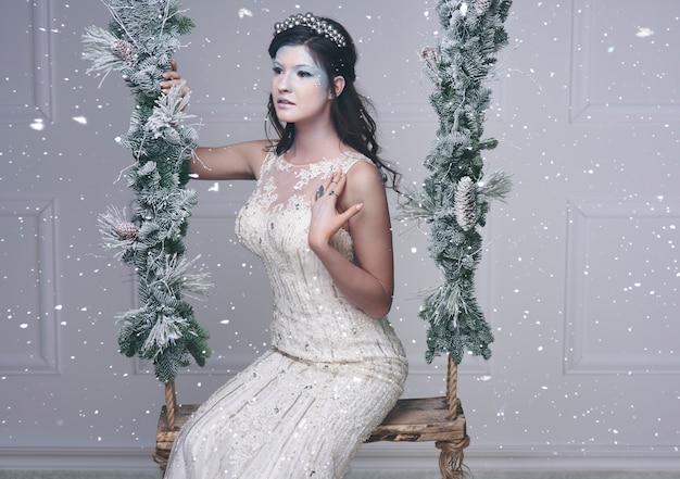 Schneekönigin auf holzschaukel unter fallendem schnee