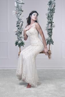 Schneekönigin auf schaukel posiert