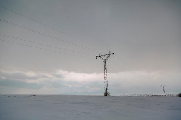 Schneelandschaft des winters mit elektrischen säulen im feld