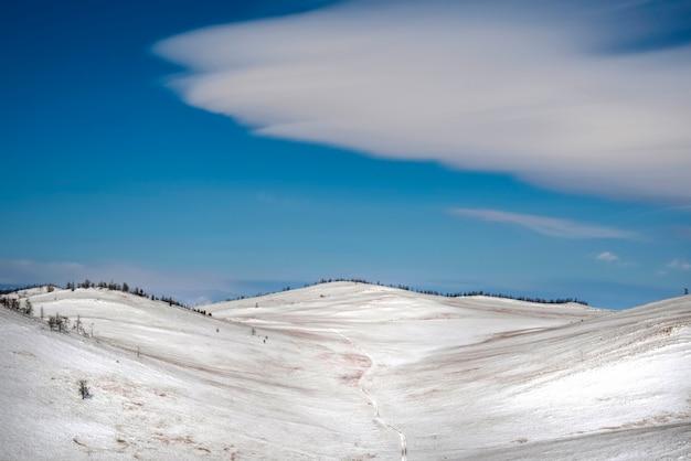 Schneelandschaft des winters mit linsenförmigen wolken, blauer himmel. desktop-hintergrund irkutsk region, russland