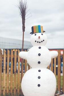 Schneemann mit einem topf und besenstiel bewölkten tag