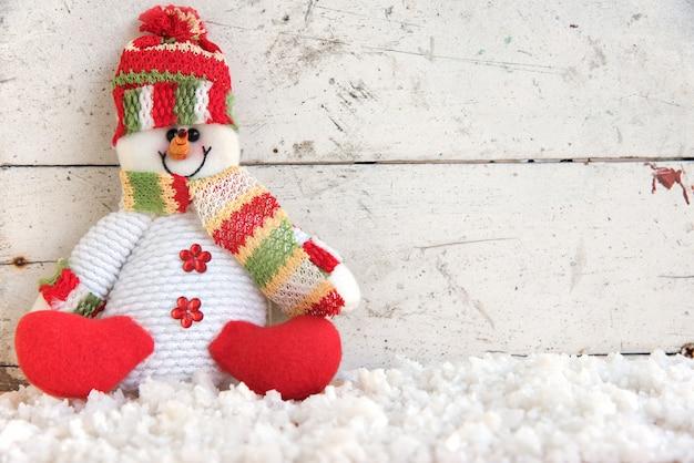 Schneemann sitzt auf schnee