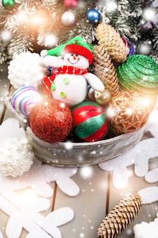 Schneemann-spielzeug im korb mit weihnachtsbällen. lichtmagie-effekte, schnee zeichnen.