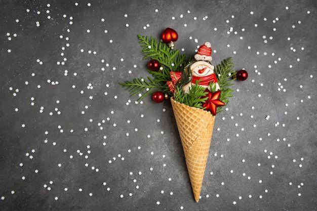 Schneemann, thuja-zweige und weihnachtsspielzeug in einem waffelkegel. dunkelgraue wand mit schneeflocken. ein originelles süßes geschenk.