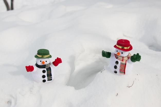 Schneemann und freund stehen zwischen schneehaufen im park. die morgensonne erwärmt sich im winter. willkommene weihnachtszeit.