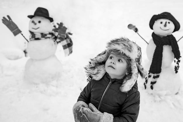 Schneemann und lustiges kind der freund steht in wintermütze und schal mit roter nase. fröhlich