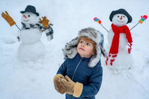 Schneemann und lustiges kind der freund steht in wintermütze und schal mit roter nase frohe weihnachten...