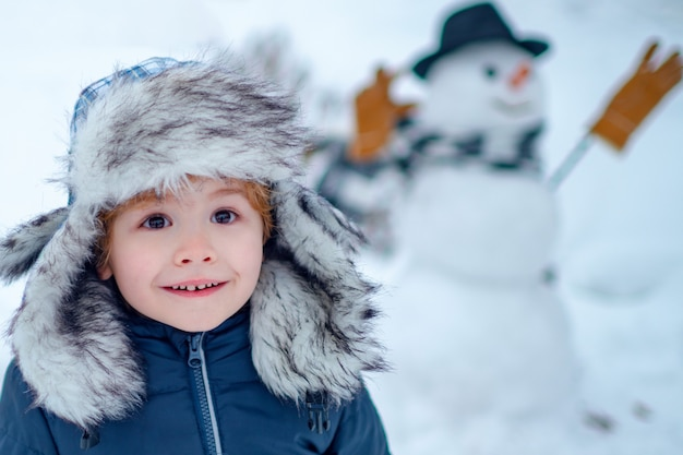 Schneemann und lustiges kind der freund steht in wintermütze und schal mit roter nase. schneemann machen
