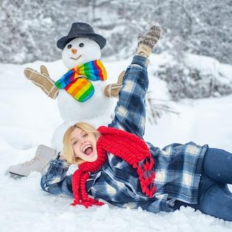 Schneemann und lustiges mädchen im winter draußen. netter schneemann in einem verschneiten dorf.