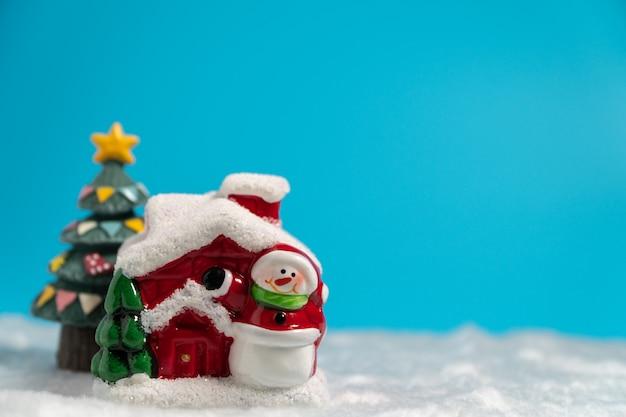 Schneemann und rotes haus und weihnachtsbaum auf dem schnee.
