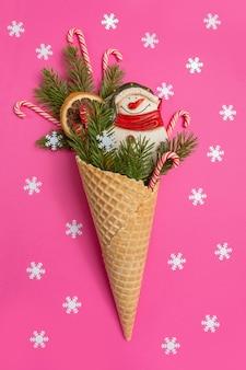Schneemann, weihnachtsbaumzweige und lutscher in einem waffelkegel. rote wand mit schneeflocken. ein originelles süßes geschenk.