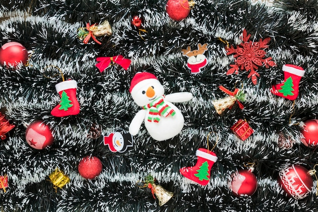 Schneemann zwischen weihnachtsspielwaren auf lametta