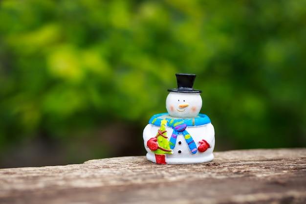 Schneemannfigur auf einem holztisch im freien