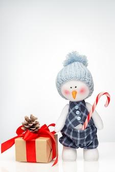 Schneemannpuppe und weihnachtsgeschenkbox mit einem hellen farbverlauf blau