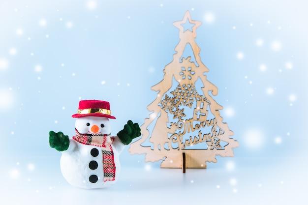 Schneemannstand nahe weihnachtsbaum, frohen weihnachten und guten rutsch ins neue jahr