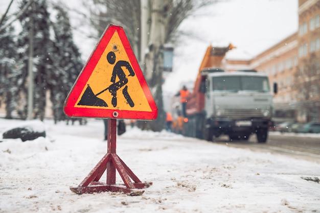 Schneepflug entfernen schnee von der stadtstraße. warnung verkehrsschild. winter service fahrzeug schneefräse arbeiten. reinigung schneebedeckter gefrorener straßen.