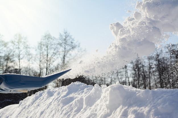 Schneeschaufeln am sonnigen wintertag. schneeräumen von der auffahrt
